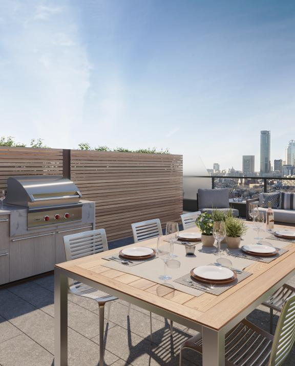 Sunny day on a rooftop patio with views of the Boston skyline at the Quinn