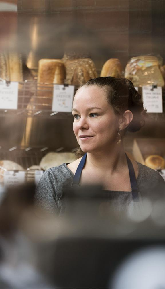 Woman standing in bakery with apron in front of freshly made bread