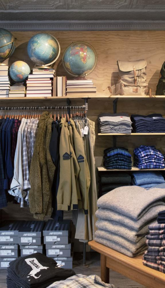 Inside a clothing shop in Boston featuring sweaters, shirts and backpacks
