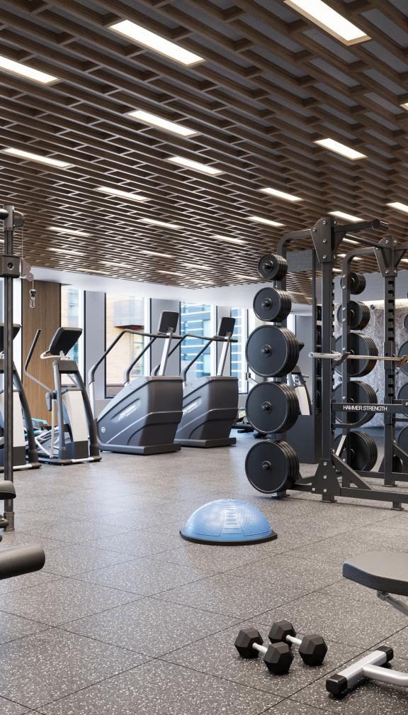 The Quinn fitness center with Hammer Strength squat racks and a built in rock climbing wall